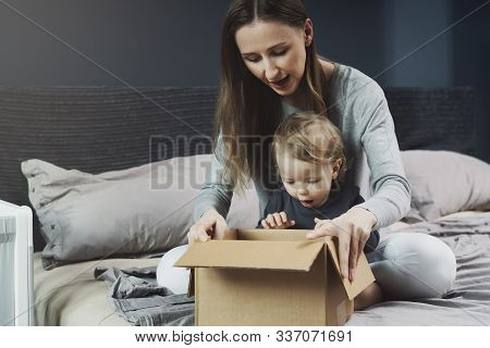 Woman And Baby Unpacking Cardboard Box With Surprise. International Shopping With Shipment Worldwide