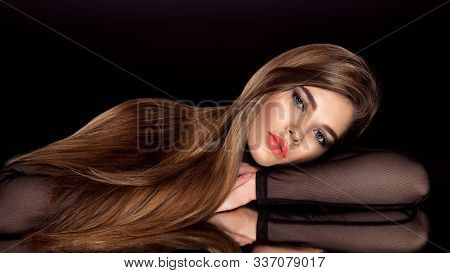 Woman with beauty long brown hair. Fashion model with long straight hair. Fashion model with a smokey makeup. Pretty woman with orange color lipstick on lips. Pantone 2019.