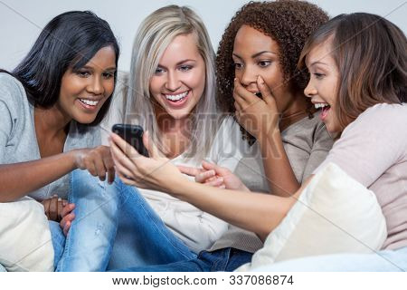 Mixed race interracial group of young female friends girls looking at social media on mobile smart cell phone and laughing having fun
