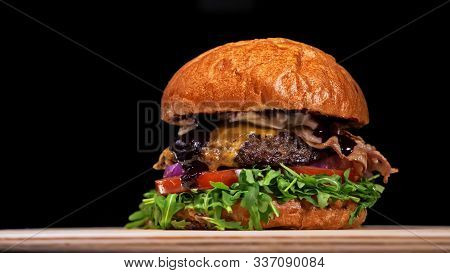 Craft Burger Is Cooking On Black Background. Consist: Sauce, Arugula, Tomato, Onion, Bacon, Currant