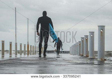 Surfing As A Lifestyle. Surfers Putting On Wetsuits Go Along The City Pier To The Sea. Concept: Wint