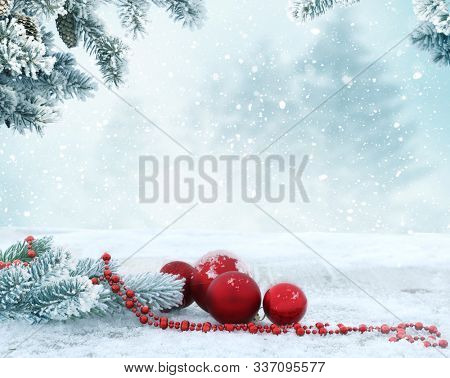 Holiday background with red Christmas balls and fir tree branch. Winter Scene. New Year greeting card.