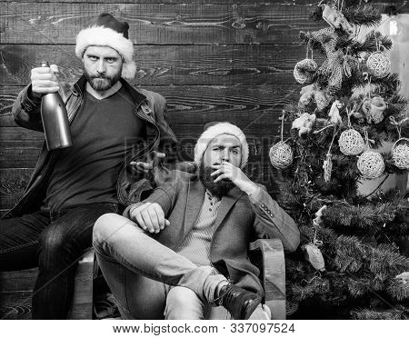 Men Drink Champagne And Smoking. Brutal Men Celebrate New Year Near Christmas Tree. New Years Resolu