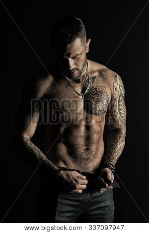 Man With Tattoo Design On Skin. Bearded Man Shirtless With Fit Torso. Fashion Model Buckle Leather B
