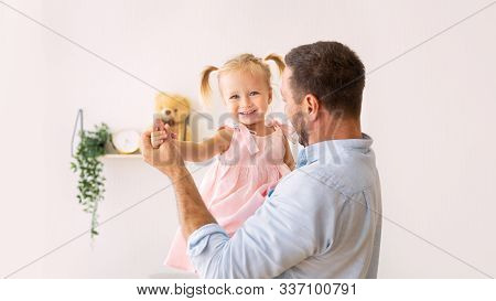 Babysitting Concept. Cheerful Dad Dancing With His Cute Little Daughter. Copy Space, Panorama