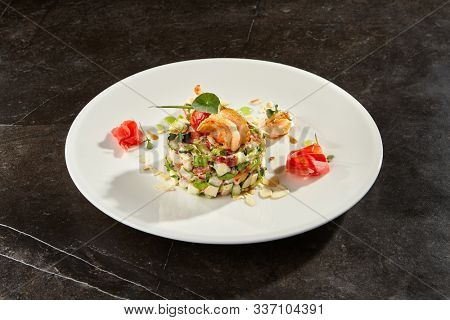 Olivier salad with crab meat and shrimps on white plate. Traditional Russian New Year Eve dish. Christmas festive meal on scratchy black table. Delicious salad with seafood and mayonnaise