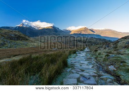 Early Morning Light And Shadow Over Mountains And Snow. Y Garn And  Glyder Farw. Stone Path Up To Cw
