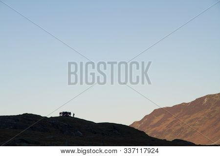 Silhouette Of Group Of People On Hill, Cannot Be Identified. Morning Lit Mountainside Behind. Cwm Id