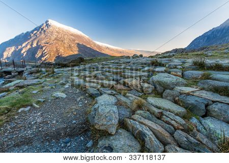 Early Morning Light And Shadow Over Mountains And Snow. Stone Path In Foreground And Mountain  Carne