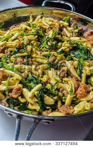 Italian Spicy Sausage Ricotta Cavatelli Pasta And Broccoli Rabe Simmering On Kitchen Stove