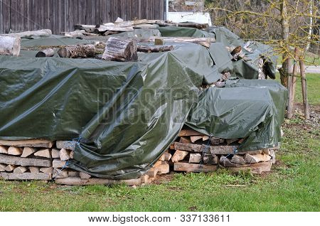 Large Heap Of Fuel Wood On A Farmyard Covered With A Green Tarpaulin