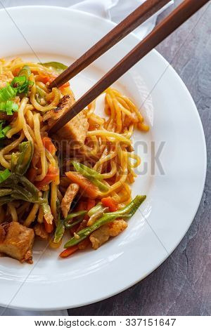 Eating Japanese Chicken Yakisoba Noodles With Chopsticks