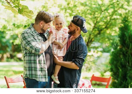 Fathers Hugging With Their Daughter. Family Walking In The Park