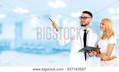 Doctor With Patient Pointing At Empty Copy Space.