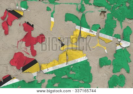 Guyana flag depicted in paint colors on old obsolete messy concrete wall closeup. Textured banner on rough background poster