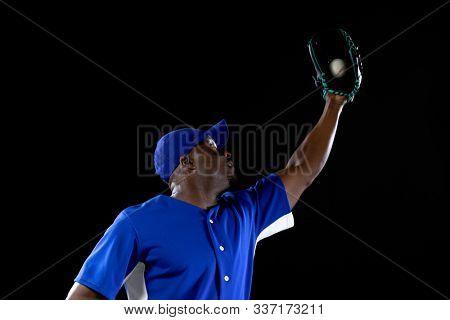 Front view of an African American male baseball player, a fielder wearing a team uniform, baseball cap and a mitt holding a caught baseball