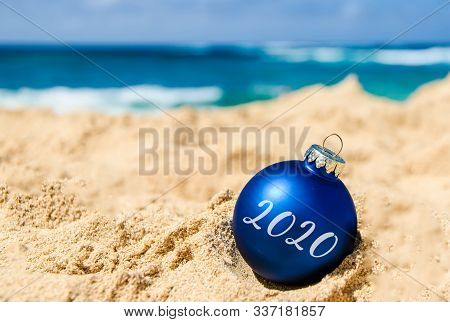 2020 Happy New Year Background With Gift And Ball On The Tropical Beach Near Ocean In Hawaii