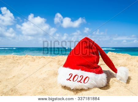 2020 Happy New Year Background With Santa Claus Hat On The Tropical Beach Near Ocean In Hawaii