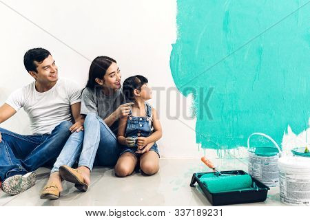Happy Family Using A Paint Roller And Painting Walls In Their New Home
