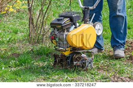 Cultivator For Tillage In The Garden,motor Cultivator. Man Farmer Plows The Land With A Cultivator.