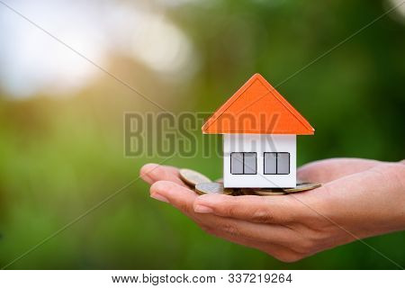 Orange Roof Houses And Coins Are In The Hands Of Businessmen. The Concept Of Home Insurance Insures