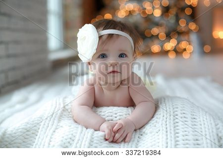Lovely,beautiful Newborn Girl Lying On A White Blanket With A White Flower On His Head,new Year And