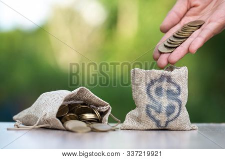 Sack Bags And Coin Bags Are Placed Close To Each Other, With The Hands Of Businessmen Going To Drop