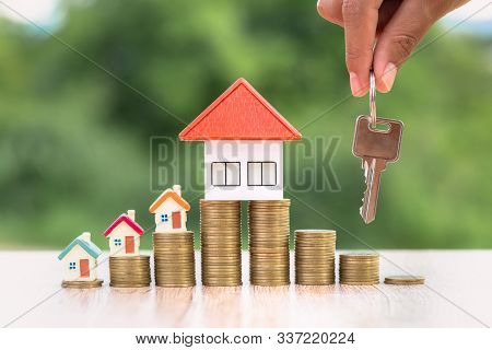 Real Estate Agents Hold House Keys For Clients. House On The Coin Ladder Ideas For Real Estate, Mobi