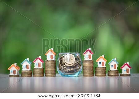 House On The Coin Ladder. A Coin In A Glass Bottle.concept Of Saving Money To Buy A House. Save Mone
