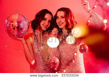 Sister Twins On Party With Red Light, Disco Ball And Lens Flare