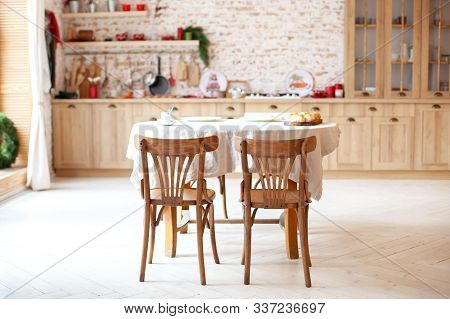Dining Room In A Cottage Style. Brown Kitchen With A Round Rustic Dining Table With Chairs. Outdoor