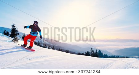 Bright Young Snowboarder Riding Red Snowboard in the Mountains at Sunny Day. Snowboarding and Winter Sports
