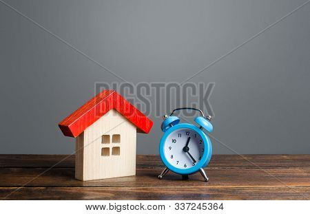Wooden House And Alarm Clock. Mortgage And Loan Concept. Temporary Rental Housing And Residence Perm