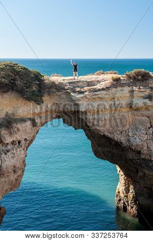 A Young Woman Standing And Waving On Natural Arch Above Ocean, Arco De Albandeira, Algarve, Portugal