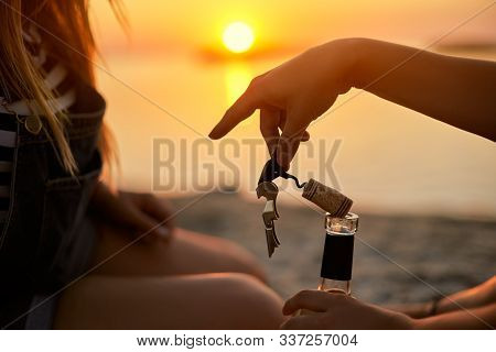 Woman Hand Gracefully Opens A Bottle Of White Wine With Corkscrew And Takes Out A Cork Bung. Female