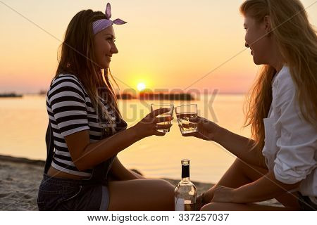 Women Clink Glasses With White Wine On The Beach. Girlfriends Cheerfully Celebrate Vacation And Proc