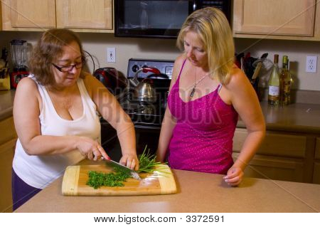 Women Chopping Food In The Kitchen