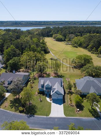 Aerial view of beautiful home on golf course and river.