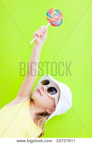 Adorable little girl with lollipop over colorful wall