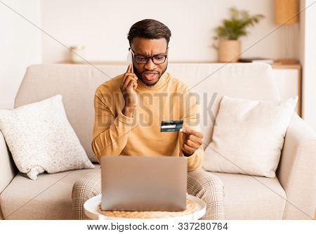 Discontented Black Man Calling To Bank Solving Problems With Credit Card Shopping Online On Laptop A