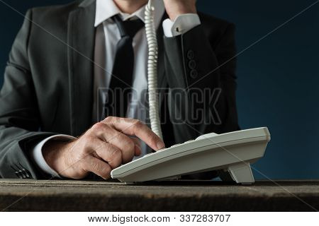 Front View Of Businessman In Elegant Suit Dialing A Telephone Number Using White Landline Phone.
