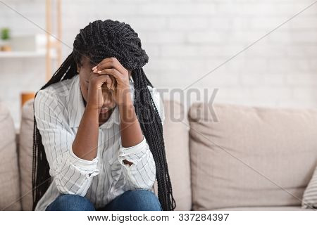 Despair. Upset Black Woman Sitting Alone At Home, Touching Her Head In Despair, Selective Focus