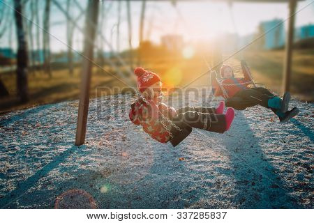 Boy And Girl On Swings In Outdoor Playground, Kids Play Outside