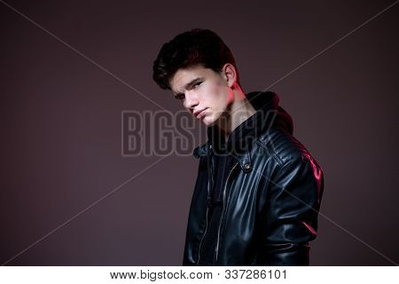 Attractive Young Guy Posing In Studio. Young Caucasian Guy Model In Black Clothes Posing In The Stud