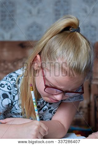 A Little Girl With A Tail Of 6 Years Of European Appearance In Glasses, Does Homework, Drawer, Does