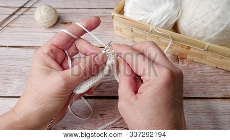 Female Hands With Knitting White Color, Needles And Knitted Thing In The Process Of Knitting Next To