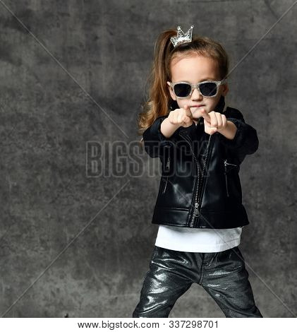 Cool Frolic Kid Girl With Silver Crown Hairpin And In Leather Jacket And Sunglasses Is Pointing Fing