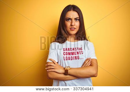 Beautiful woman wearing fanny t-shirt with irony comments over isolated yellow background skeptic and nervous, disapproving expression on face with crossed arms. Negative person.