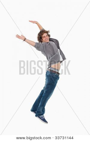 Happy male student posing by jumping against white background
