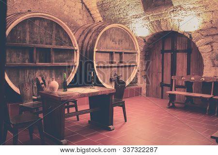 Old Oak Barrels In An Ancient Wine Cellar. Ancient Wine Cellar In The Ancestral Castle For Wine Tast